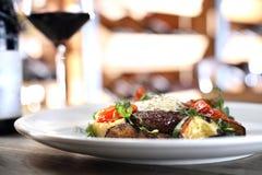 Entrecote牛排用草本黄油和烤菜服务与一杯红酒 库存图片
