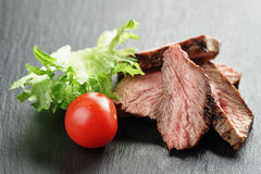 Entrecote beef steak sliced on slate board with vegetables Stock Photos