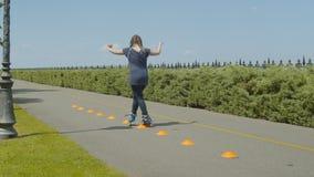 Entrecruzamiento femenino del patinaje sobre ruedas a través de conos almacen de video