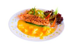 Entree of salmon steak. An isolated view of an entree plate of fresh, grilled Alaskan King Salmon steak with garnish.  White background Royalty Free Stock Images