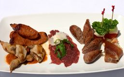 Entree Tasting Plate. An Entree selection plate offering Roasted Quail, Italian Sausages, Beef Carpaccio, Prosciutto, Tomato, and Bocconcini Stock Photo