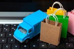 Entrega de órdenes de la tienda en línea Bolsos de compras en el camión de reparto del teclado y del mensajero del ordenador port fotografía de archivo libre de regalías