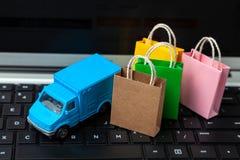Entrega de órdenes de la tienda en línea Bolsos de compras en el camión de reparto del teclado y del mensajero del ordenador port imagen de archivo libre de regalías