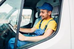 Entrega del cargo, mensajero del conductor que se sienta en el camión Imagen de archivo