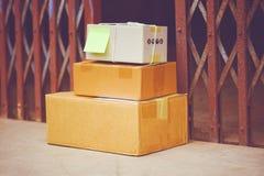Entrega del comercio electrónico que hace compras en línea y concepto de la orden - paquetes entregados en piso cerca del acero d imagen de archivo libre de regalías