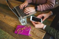Entrega el ordenador portátil y el smartphone en la tabla de madera con los vidrios Imagenes de archivo