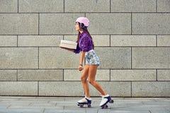 Entrega en pcteres de ruedas de la muchacha hermosa en casco Fotografía de archivo libre de regalías