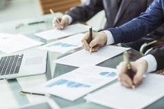 Entrega a equipe do negócio que trabalha com planos financeiros Imagem de Stock Royalty Free