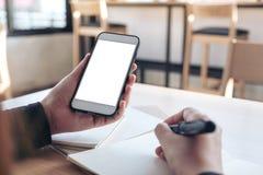 Entrega guardar o telefone celular branco com a tela branca vazia ao escrever no caderno no escritório foto de stock
