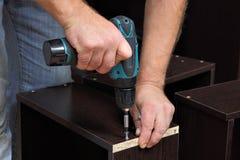 Entrega o carpinteiro com chave de fenda, apertam o parafuso nas gavetas do ch Foto de Stock