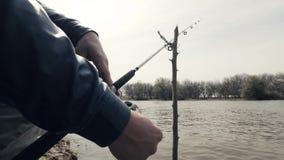 Entrega o carretel de giro da pesca do pescador na haste durante peixes cortantes na água do rio filme