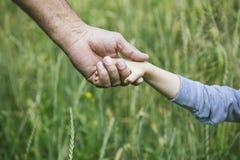 Entrega o close up de uma criança pequena e de uma pessoa idosa para ficar o tog Fotografia de Stock Royalty Free