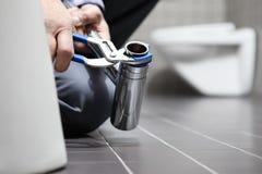 Entrega o encanador no trabalho em um banheiro, sondando o serviço de reparações, como imagem de stock