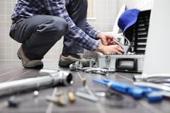 Entrega o encanador no trabalho em um banheiro, sondando o serviço de reparações, como fotografia de stock royalty free