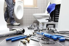 Entrega o encanador no trabalho em um banheiro, sondando o serviço de reparações, como fotos de stock royalty free