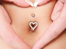 Entrega o símbolo do coração em torno da perfuração do umbigo Foto de Stock Royalty Free