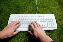 Entrega o teclado de dactilografia na grama Imagens de Stock
