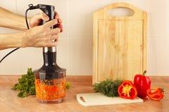 Entrega vegetais shredded cozinheiros chefe no misturador Imagem de Stock Royalty Free