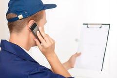 Entregador que fala no telefone celular Fotografia de Stock Royalty Free