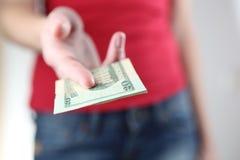 Entregar da mulher nova/que dá lhe o dinheiro Fotos de Stock Royalty Free