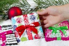 Entregar pegarando o feriado envolveu o presente para o Natal fotos de stock