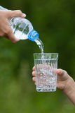 Entregue a água de derramamento da garrafa no vidro Imagens de Stock