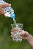 Entregue a água de derramamento da garrafa no vidro Foto de Stock Royalty Free