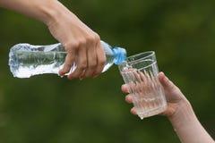 Entregue a água de derramamento da garrafa no vidro de uma outra pessoa Imagens de Stock Royalty Free