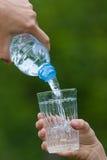 Entregue a água de derramamento da garrafa no vidro no backgroun verde Imagens de Stock Royalty Free