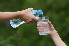 Entregue a água de derramamento da garrafa no vidro no fundo da natureza Fotografia de Stock