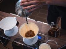 Entregue a água de derramamento de Barista do café do gotejamento na borra de café com filtro fotografia de stock
