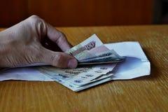 Entregue a abertura de um envelope completamente do rublo de russo da moeda do russo, da RUB como um símbolo da lavagem de dinhei Imagens de Stock Royalty Free