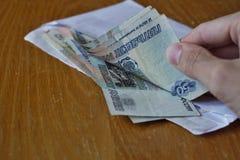 Entregue a abertura de um envelope completamente do rublo de russo da moeda do russo, da RUB como um símbolo da lavagem de dinhei Foto de Stock Royalty Free