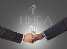 Entregue a agitação entre um homem de negócios com dinheiro do dólar para a ideia de s Fotografia de Stock Royalty Free
