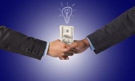 Entregue a agitação entre um homem de negócios com dinheiro do dólar para a ideia de s Imagem de Stock Royalty Free