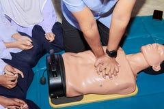 Entregue a bomba de Heart do estudante com o manequim médico no CPR, no treinamento de refresher da emergência à assistência do m fotografia de stock