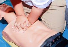 Entregue a bomba de Heart do estudante com o manequim médico no CPR, no treinamento de refresher da emergência à assistência do m imagem de stock