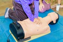 Entregue a bomba de Heart do estudante com o manequim médico no CPR, no treinamento de refresher da emergência à assistência do m fotos de stock
