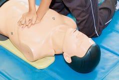Entregue a bomba de Heart do estudante com o manequim médico no CPR, no treinamento de refresher da emergência à assistência do m foto de stock royalty free