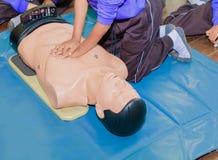 Entregue a bomba de Heart do estudante com o manequim médico no CPR, no treinamento de refresher da emergência à assistência do m imagem de stock royalty free