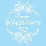 Entregue a caligrafia o dia de mãe feliz branco com flores e folhas em um fundo azul Cartão do vintage Foto de Stock Royalty Free