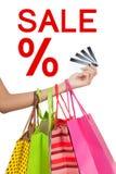 Entregue cartões de crédito da mostra com os sacos de compras com sinal da venda Foto de Stock Royalty Free