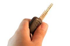 Entregue a chave e o controlo a distância do carro da posse no fundo branco Fotografia de Stock