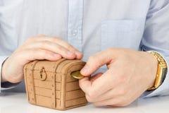 Entregue a colocação da moeda em uma dinheiro-caixa Foto de Stock Royalty Free