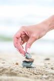Entregue a colocação da pedra na pirâmide na areia Mar no fundo Fotografia de Stock Royalty Free