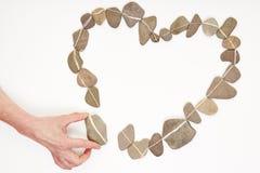 Entregue a colocação da pedra no coração do amor Foto de Stock Royalty Free