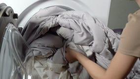 Entregue a colocação da roupa na máquina de lavar vídeos de arquivo