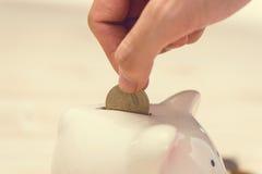 Entregue a colocação de moedas douradas em um mealheiro cor-de-rosa Ienes japoneses foto de stock royalty free