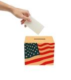 Entregue a colocação de um Bollot de votação na caixa. Imagens de Stock