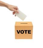 Entregue a colocação de um Bollot de votação na caixa. Imagem de Stock